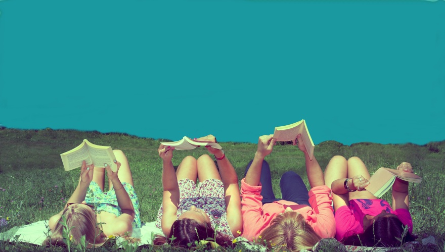 friends reading under sunshine lying on the meadow