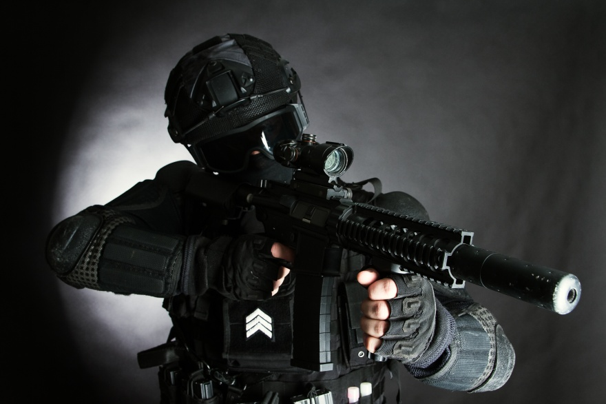 Member of the SWAT squad with an assault rifle in a black uniform on dark background. Special weapons and tactics. Special Forces.
